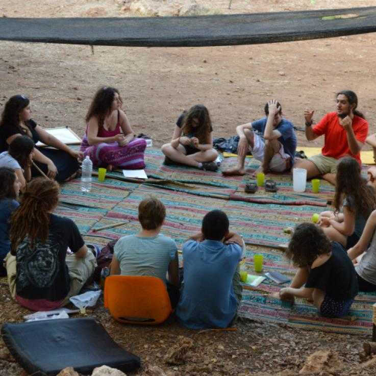 Young people sit around in a circle talking