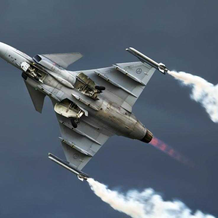 A fighter aircraft in the air during a display. The image is shot from below, and the aircraft has plumes of smoke trailing from the tip of each wing.