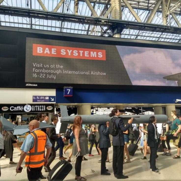A train station lobby. A huge advertisement for BAE Systems is in the background. In the fore ground stands a line of activists dressed in suits, carrying a hgue missile on their shoulders.