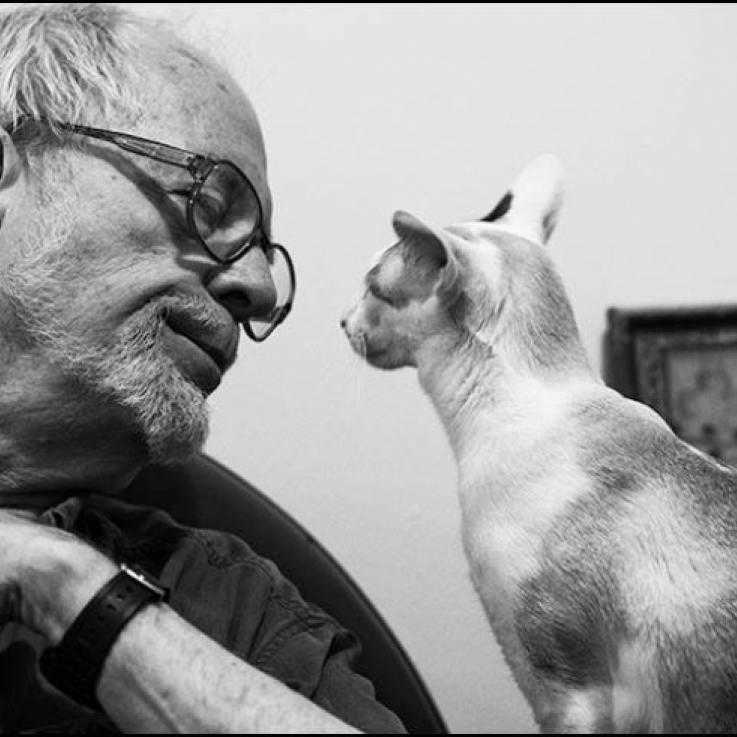 David McReynolds on the left side of the photo, wearing glasses, looking at a cat sat on the right.