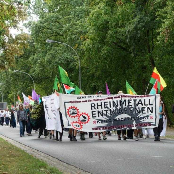 "A large group of people march down a street. The front group are holding a banner reading ""disarm Rheinmetall"" in German"