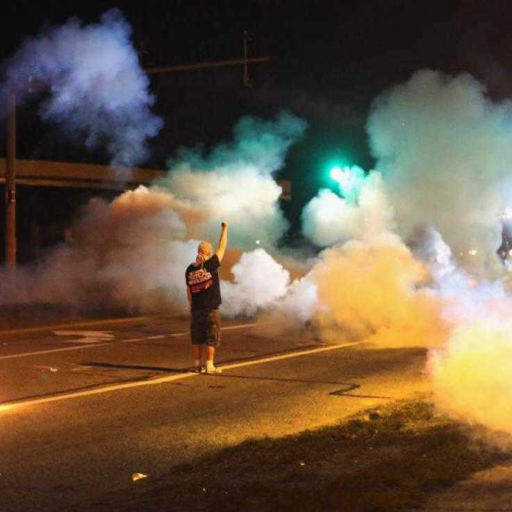 A man stands still with his arm raised amid a cloud of tear gas at night