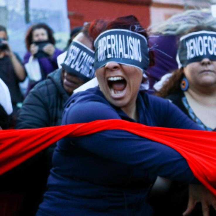 "A protest. A woman in the fore ground is asked wit h the word ""imperialism"". She is throwing a red cloth. Behind her are other masked protesters."