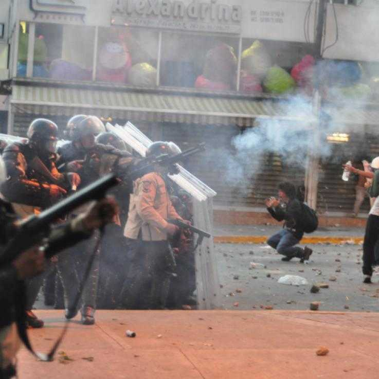 A number of police officers with tear gas launchers fire canisters towards a crowd