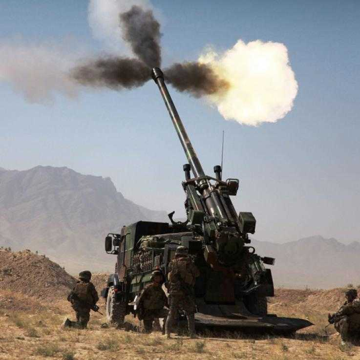 A large cannon is fired in desert terrain. A number of soldiers stand around the side.