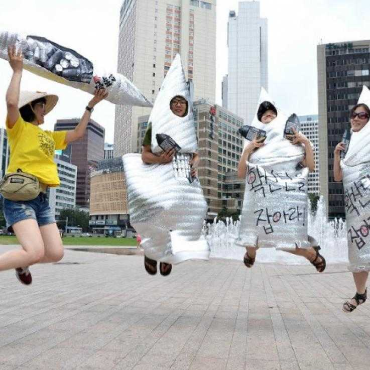 Four activists dressed as cluster munitions jump in the air