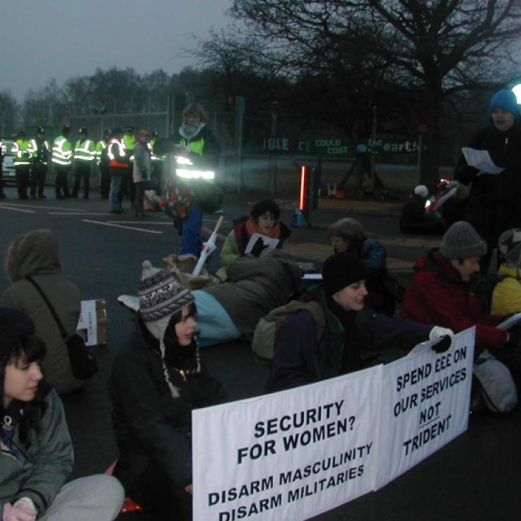 Women sit across a road in a protest against nuclear weapons. They are holding signs